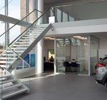 Zdjecie z daleka nowoczesnych schodow drewnianych ze szklana balustrada wykonane przez firme Vitroglass