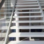Zdjecie z bliska schodow drewnianych ze szklana balustrada firmy Vitroglass