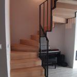 Kręcone solidne drewniane schody z metalowa balustrada firmy Vitroglass