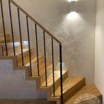 Drewniane schody z metalowa balustrada i drewniana rączka firmy vitroglass
