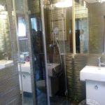 łazienka z nowoczesna ścianka i szklanymi drzwiami do kabiny