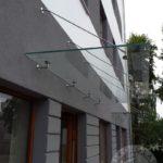 daszek szklany wiszący na metalowych drutach nad drzwiami