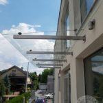 szklany daszek z metalowymi elementami nad drzwiami