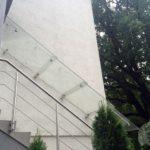 daszek szklany nad schodami z metalowymi elementami