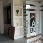 szklana ścianka z nadrukiem i drzwiami z logiem firmy i paskami