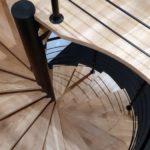 widok z góry kręconych drewnianych schodów z metalowa czarna balustrada