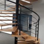 widok z boku drewnianych schodów z metalowa balustrada