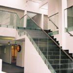 Balustrada szklana z elementami czarnego metalu do schodów