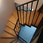 Widok z góry drewnianych schodów z metalowa balustrada firmy Vitroglass